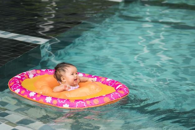 La bambina del primo piano si siede in una barca per i bambini con il fronte di sorriso nei precedenti della piscina con lo spazio della copia