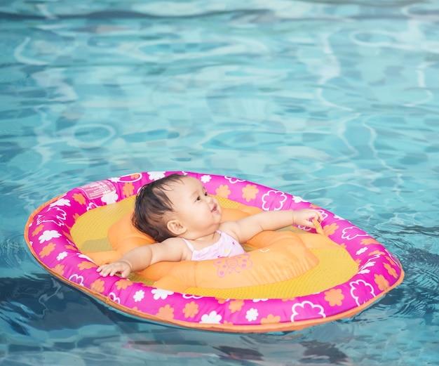 La bambina del primo piano si siede in una barca per i bambini nei precedenti della piscina con lo spazio della copia