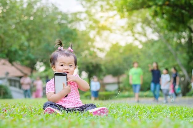 La bambina del primo piano si siede sul pavimento dell'erba con il telefono cellulare in sua mano nel parco con il fondo della luce del sole nel moto sveglio