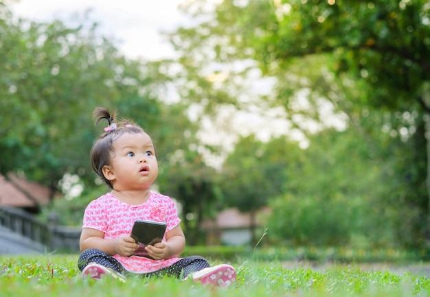 La bambina del primo piano si siede sul pavimento dell'erba ed esamina lo spazio dell'immagine sul fondo di vista del parco