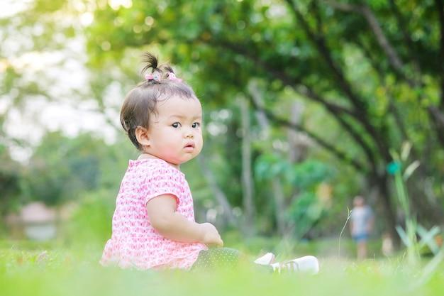 La bambina del primo piano si siede sul pavimento dell'erba nel parco con il fondo della luce del sole nel moto sveglio