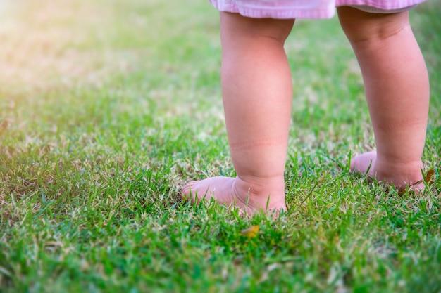 La bambina della gamba gioca la grande palla nel giardino