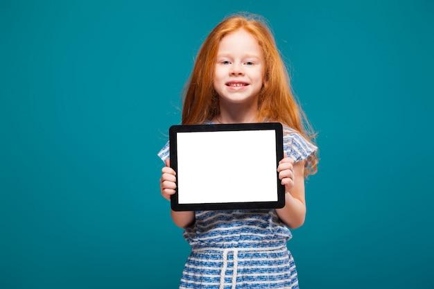 La bambina di bellezza con i capelli rossi lunghi tiene lo schermo in bianco ipad o il ridurre in pani