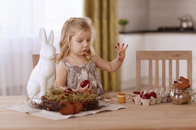 La bambina dipinge le uova di pasqua nella stanza alla tavola di festa.