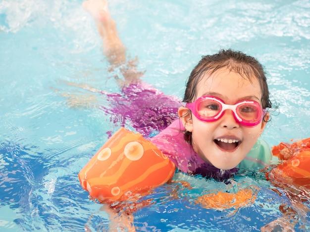 La bambina divertente che indossa una manica e gli occhiali di protezione del costume da bagno sta nuotando nello stagno.