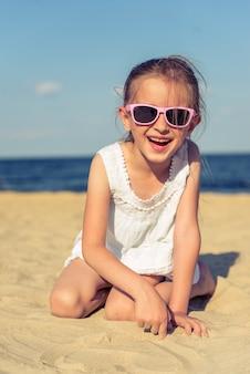 La bambina divertente in occhiali da sole sta esaminando la macchina fotografica.