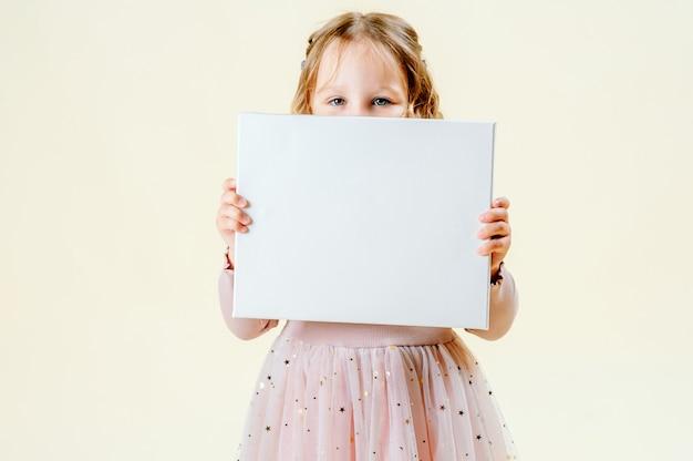 La bambina divertente tiene un segno per le iscrizioni. sfondo chiaro