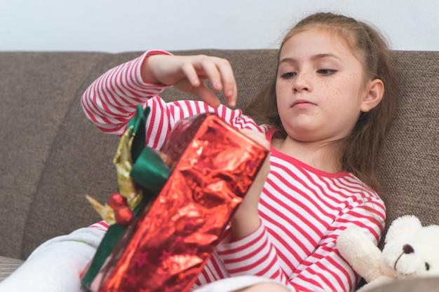 La bambina è aperta scatola regalo di natale