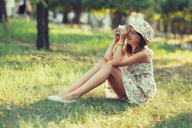 La bambina è giocata dalla macchina fotografica seduta sull'erba nel parco. fare selfie e fotografare il mondo intorno
