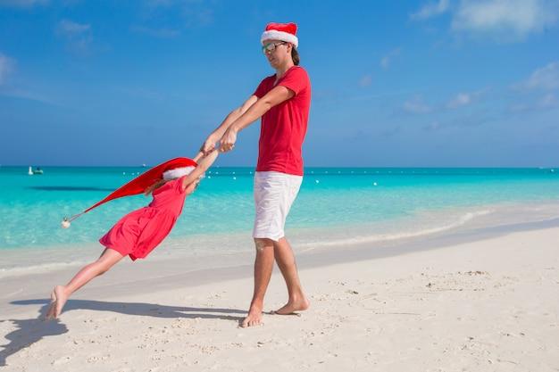 La bambina e il papà felice in santa hat si divertono alla spiaggia tropicale
