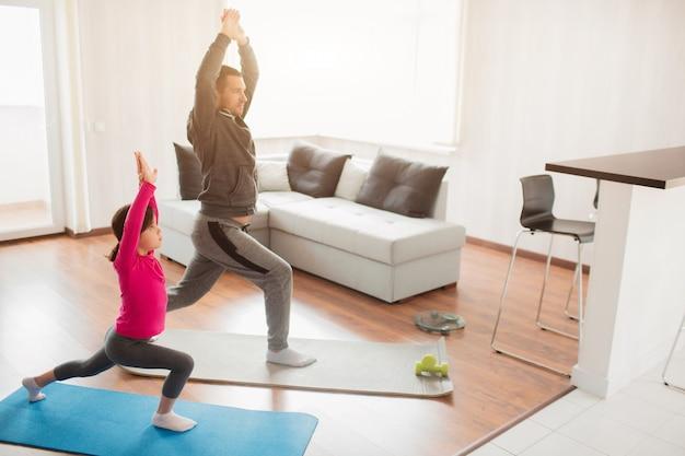 La bambina e il suo giovane padre stanno facendo un balzo in avanti dell'allenamento a casa. ragazzo carino si allena al coperto. piccolo modello femminile dai capelli scuri in abiti sportivi ha esercizi in camera
