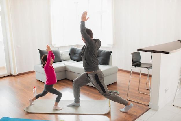 La bambina e il suo giovane padre stanno facendo un balzo in avanti dell'allenamento a casa.