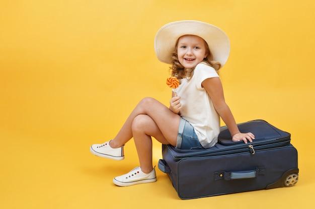 La bambina è seduta su una valigia con caramelle in mano.