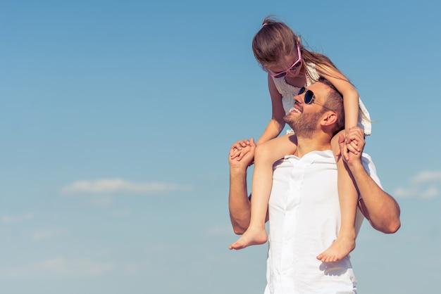 La bambina è seduta sulle spalle di suo padre