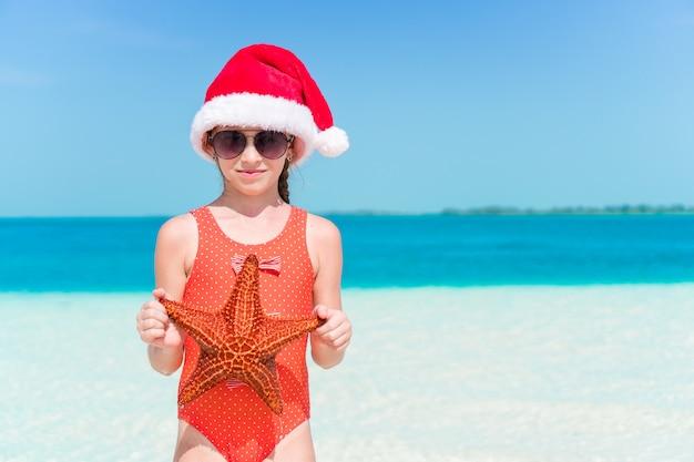 La bambina felice in cappello di santa durante le vacanze al mare di natale si diverte molto
