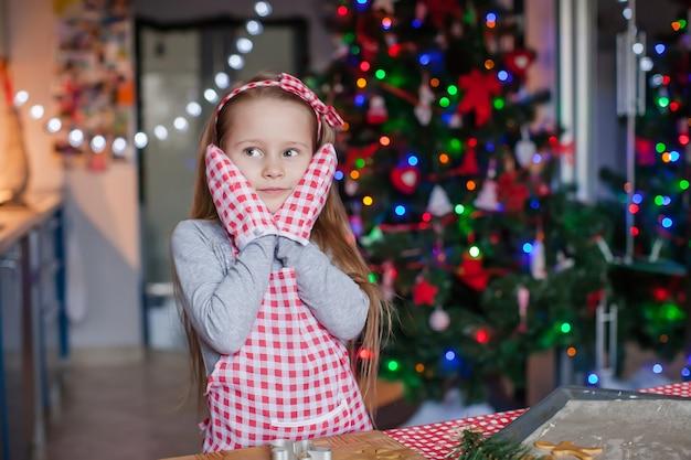 La bambina felice in guanti indossati che cuociono i biscotti del pan di zenzero di natale