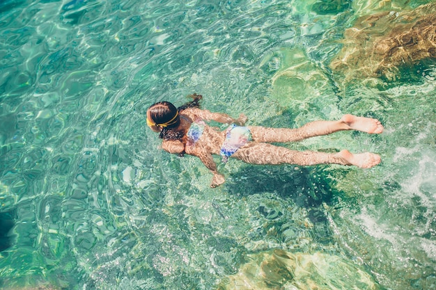La bambina felice nella maschera dello snorkeling si tuffa underwater con i pesci tropicali