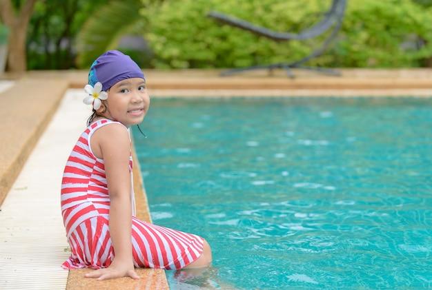 La bambina felice si siede nella piscina all'aperto