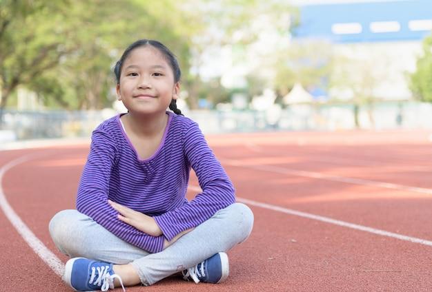 La bambina felice si siede sulla pista a stadiam,