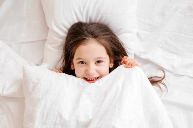 La bambina felice si trova a letto a casa la mattina. sonno sano del bambino. biancheria da letto bianca, spazio per il testo
