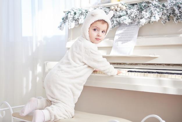 La bambina felice suona il piano il giorno di natale