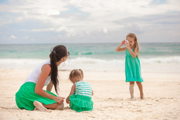 La bambina fotografa sua madre con la sorella sulla spiaggia