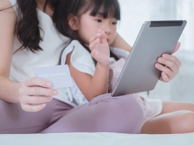 La bambina gioca a letto con sua madre