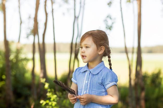 La bambina gioca con la piuma in estate nel parco