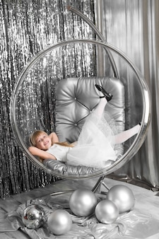 La bambina gioca su una sedia una ciotola di vetro con palline d'argento