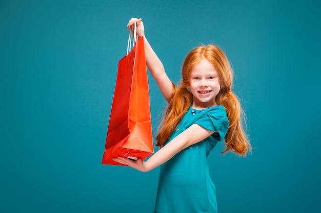 La bambina graziosa e sveglia in vestiti blu con capelli rossi lunghi tiene il pacchetto