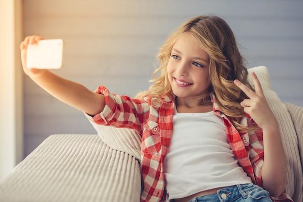 La bambina graziosa sta facendo selfie usando uno smartphone