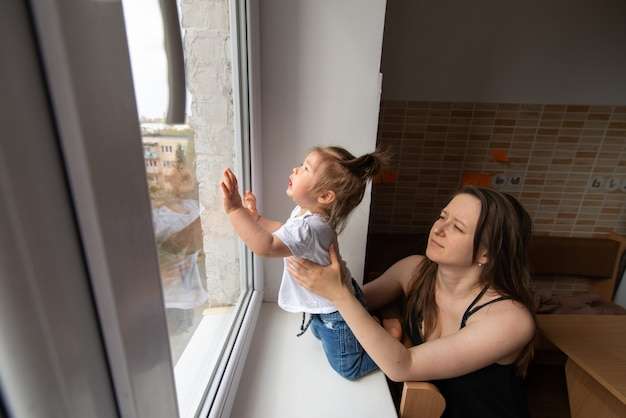La bambina guarda fuori dalla finestra e chiede fuori durante la quarantena causata dal coronavirus.