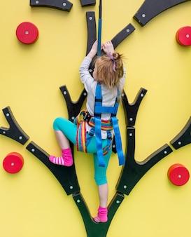 La bambina in assicurazione si prepara sulla parete rampicante