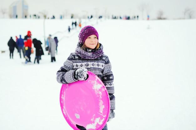 La bambina in capispalla invernale con una stampa scandinava tiene una slitta di ghiaccio e sorride contro un pendio nevoso. intrattenimento invernale