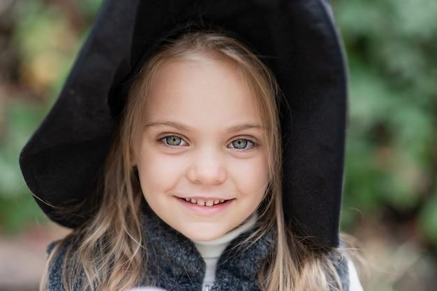 La bambina in costume della strega celebra halloween all'aperto