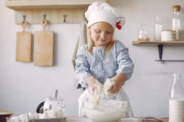 La bambina in un cappello bianco dello shef cucina l'impasto per i biscotti