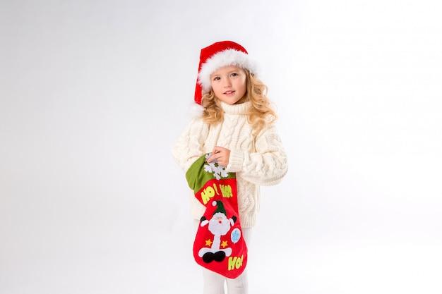 La bambina in un cappello della santa sta tenendo un calzino di natale