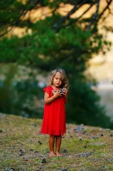 La bambina in un vestito rosso raccoglie i coni nella foresta