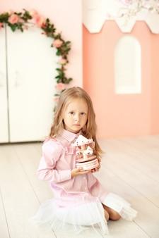 La bambina in un vestito tiene una giostra del giocattolo musicale. il bambino gioca nella stanza dei bambini. concetto di infanzia. bambino all'asilo. compleanno, celebrazione, celebrazione. il bambino riceve un regalo
