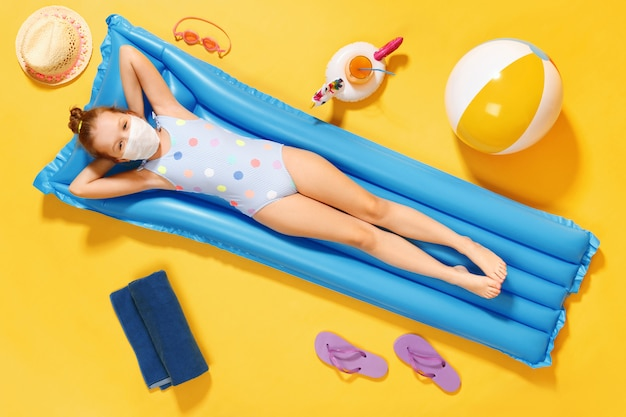 La bambina in una maschera protettiva si trova su un materasso