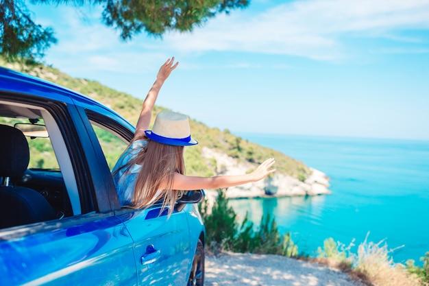 La bambina in vacanza viaggia in auto sul bellissimo paesaggio