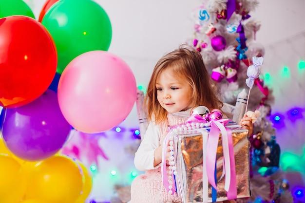 La bambina in vestito rosa gioca nella stanza con l'albero di natale rosa