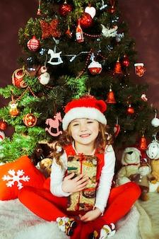 La bambina in vestito rosso si siede con una scatola attuale prima di un albero di natale