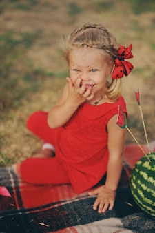 La bambina in vestito rosso si siede in un giardino e mangia le angurie