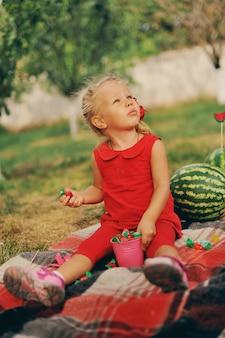 La bambina in vestito rosso si siede in un giardino vicino ad un raccolto delle angurie