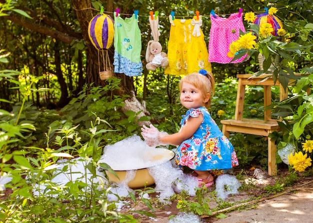 La bambina lava le cose e fa il bagno in una vasca per strada in estate
