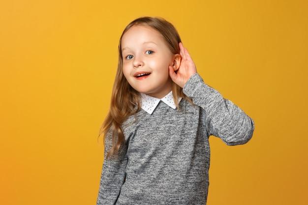 La bambina le porta una mano all'orecchio.