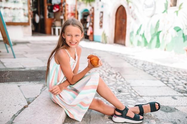 La bambina mangia croissant su vecchie strade nel villaggio europeo
