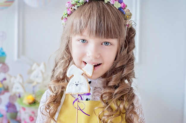 La bambina mangia un biscotto di pan di zenzero