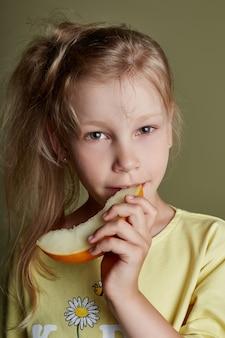 La bambina mangia un melone su uno sfondo verde, brillanti emozioni allegre